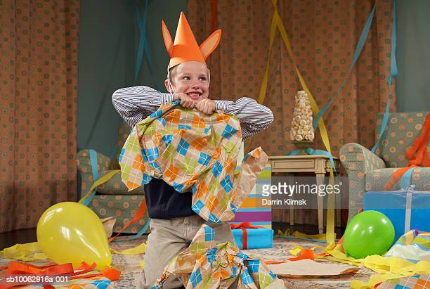 Young boy (6-7) wearing party hat, making mess in room after party