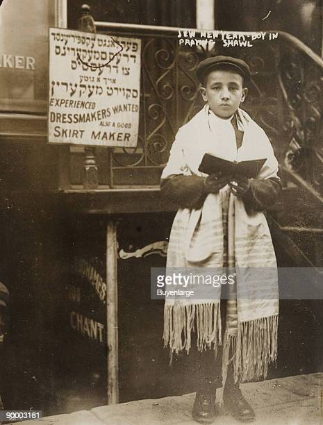 Young boy wearing prayer shawl and holding book standing outside building East Side New York City
