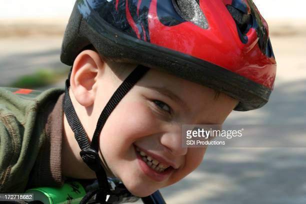 Young Boy Wearing Safety Helmet While Riding A Bike