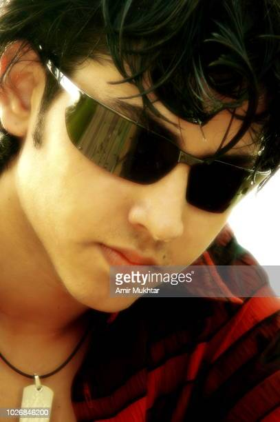 A young boy wearing sunglasses and posing for camera