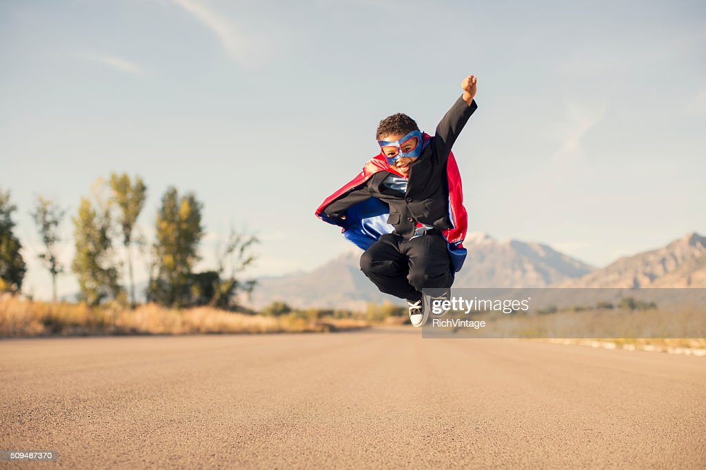 Young Boy Wearing Superhero Costume and Business Suit is Jumping : Stock Photo