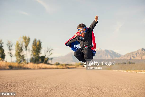Young Boy Wearing Superhero Costume and Business Suit is Jumping