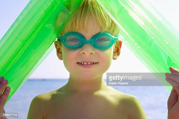 Young boy wearing swim goggles and holding an inflatable raft over his head.