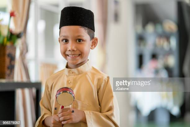 young boy wearing traditional clothes looking excited - hari raya stock pictures, royalty-free photos & images