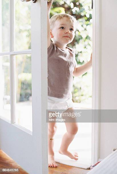 Young boy wearing T-Shirt and pants, opening a door.
