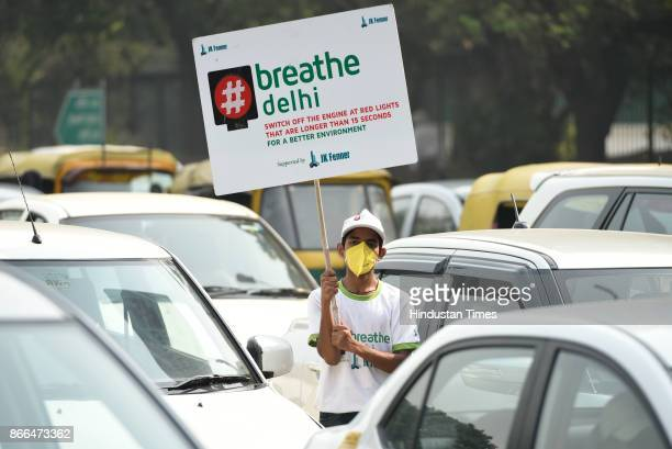 A young boy wears a mask and hold a placard to address the alarming air pollution in the national capital during a clean air campaign on October 25...