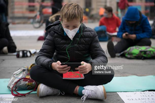 Young boy wears a protective mask and lectures with the Dad system via a smartphone during a student protest in Piazza Castello in front of the...