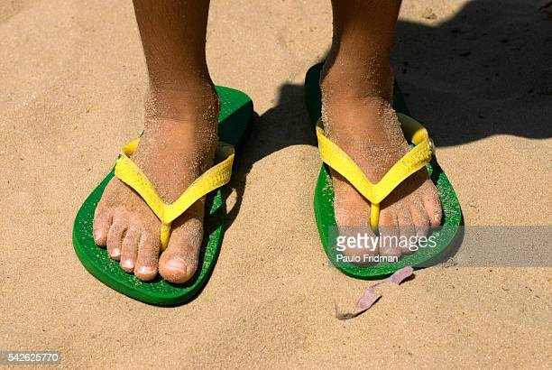 A young boy wears green and yellow Havaianas at the beach in Leblon Rio de Janeiro