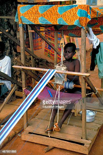 A young boy weaving traditional kente cloth a textile worn by royalty in the village of Bonwire in the Ashanti Region of Ghana West Africa
