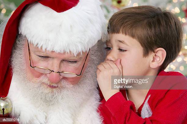 young boy whispers into father christmas' ear - santa close up stock pictures, royalty-free photos & images