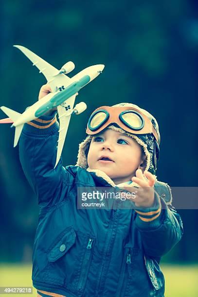 Jeune garçon avec des tenues d'aviateur et avion.