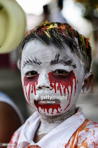 A young boy with a painted face poses before the Grebeg Ritual on August 19 2015 in Tegallalang village Gianyar Bali Indonesia During the biannual...
