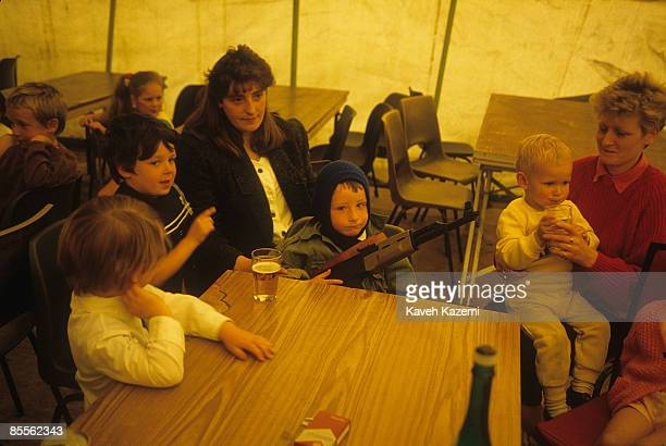 A young boy with a plastic automatic assault rifle sits with his mother and other kids during a children's festival in the Catholic residential area...