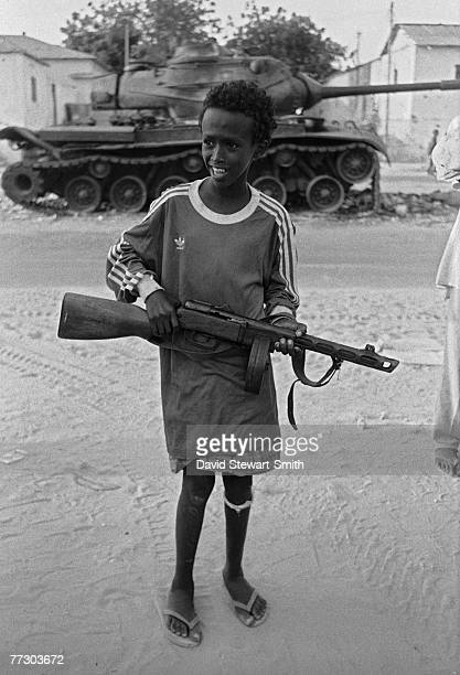 Young boy with a rifle standing in front of a tank in Mogadishu during the Somalian civil war, January 1992.