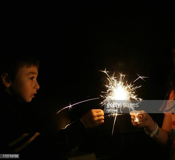 A young boy with a sparkler at night