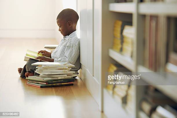 Young boy with a stack of storybooks