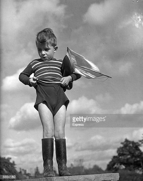 A young boy with a toy boat pulling his shorts up