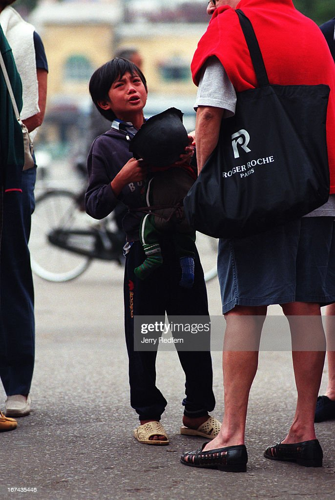 A young boy with a younger sibling strapped to his chest, begs for money from French tourists in front of the Hanoi Water Puppet Theater. It is a common spot for poor youngsters to look for handouts from foreign tourists..