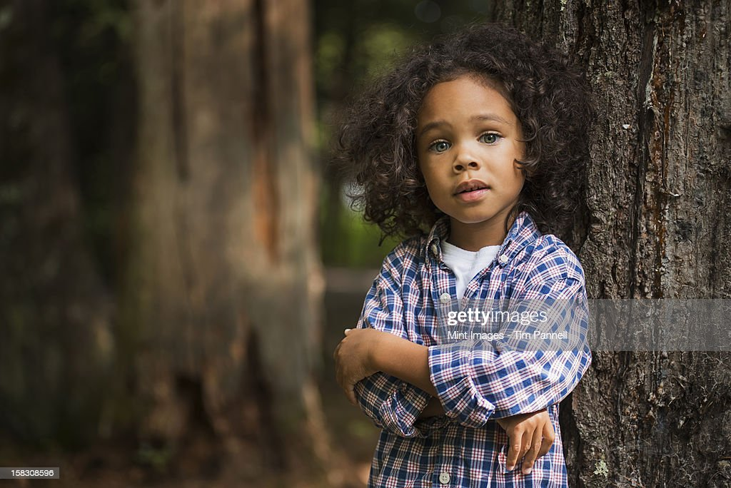 A young boy with arms folded leaning against a tree. : Stock Photo