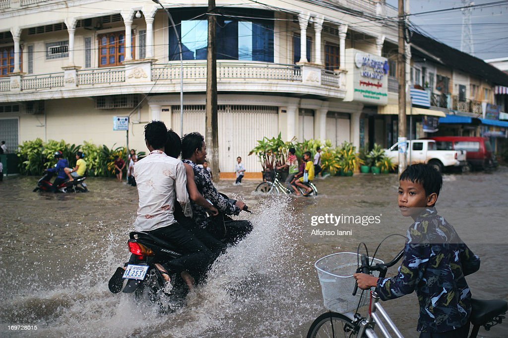 CONTENT] A young Boy with Bicycle tries to cross a flooded street by the monsoon rain in Battambang - Cambodia.