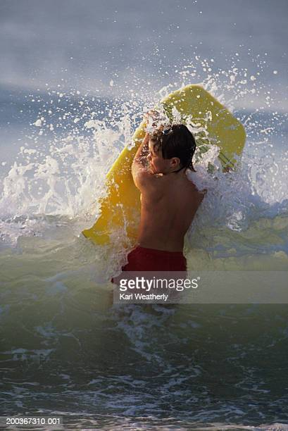 Young boy (6-7) with boogie board getting splashed in Myrtle Beach, SC