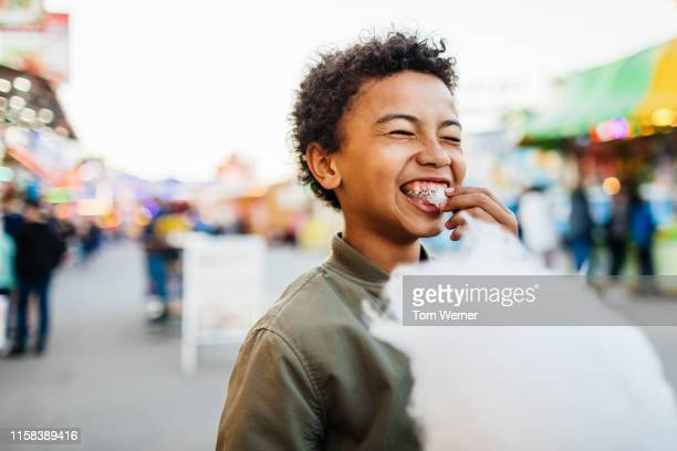 young boy with braces eating candy floss at fair - mixed race person stock pictures, royalty-free photos & images