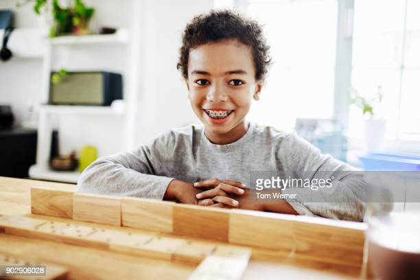 Young Boy With Braces Playing Dominoes
