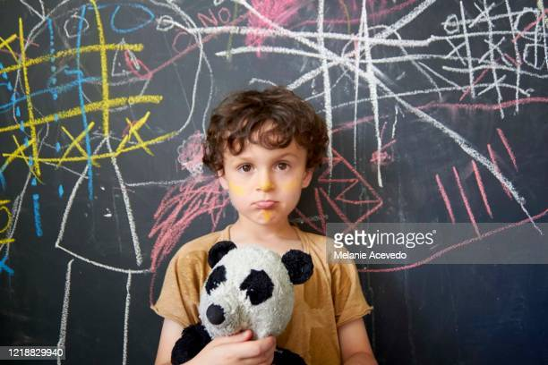 young boy with brown curly hair brown eyes holding panda standing in front of chalkboard wall with colorful chalk markings on the blackboard boy is looking at camera he is pouting - chalk outline stock pictures, royalty-free photos & images