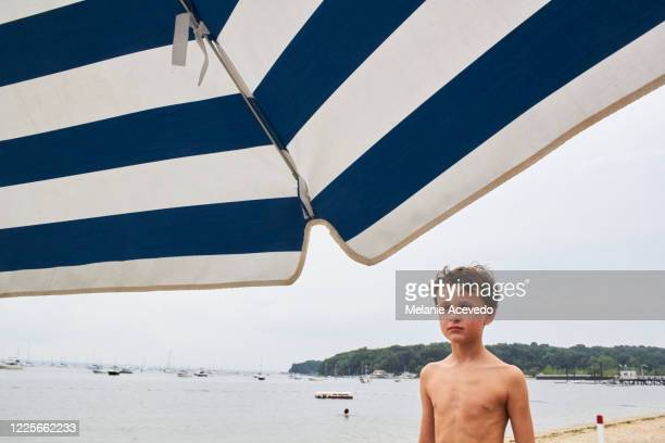 Young boy with brown curly hair brown eyes looking away from the camera striped umbrella in the top of the image boy looking into the distance shirtless water in the background horizon over the water sand and beach in the back of the photo