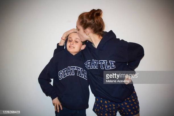 young boy with brown curly hair brown eyes with his older sister who has red hair both are standing in front of a white wall wearing matching sweatshirts posing for the camera camera flash older sister is kissing brothers head - soeur photos et images de collection