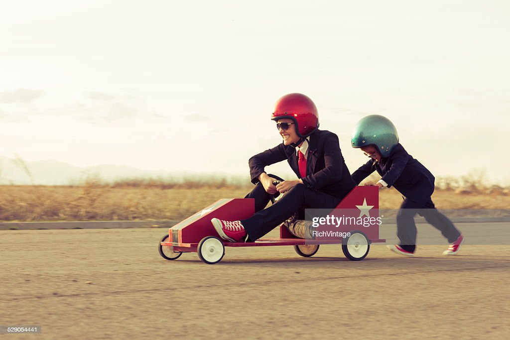 Young Boy with Businesswoman Racing a Toy Car : Stock Photo