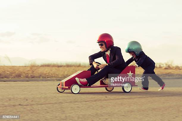 young boy with businesswoman racing a toy car - sports helmet stock pictures, royalty-free photos & images
