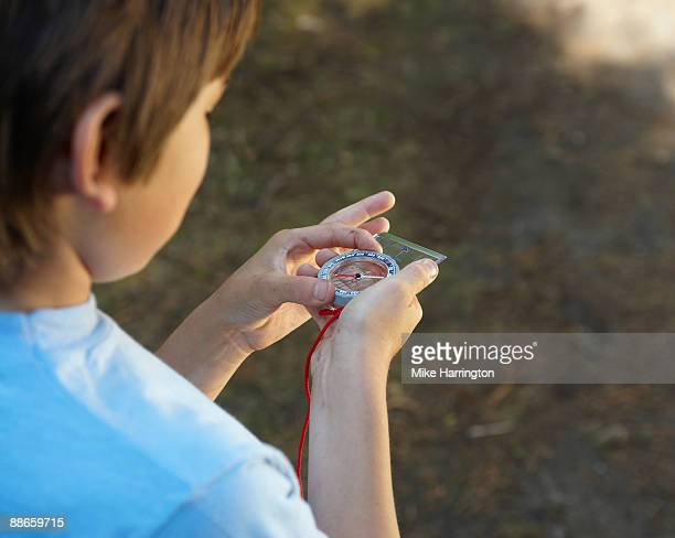 young boy with compass - compass stock pictures, royalty-free photos & images