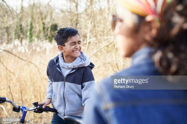 Young boy with cycle pulling face
