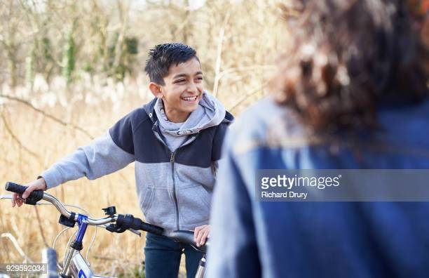 Young boy with cycle talking to friends