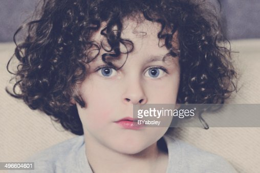 Young Boy With Dark Hair And Blue Eyes High Res Stock