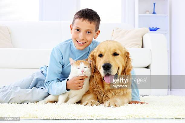 Young boy with dog and a cat.