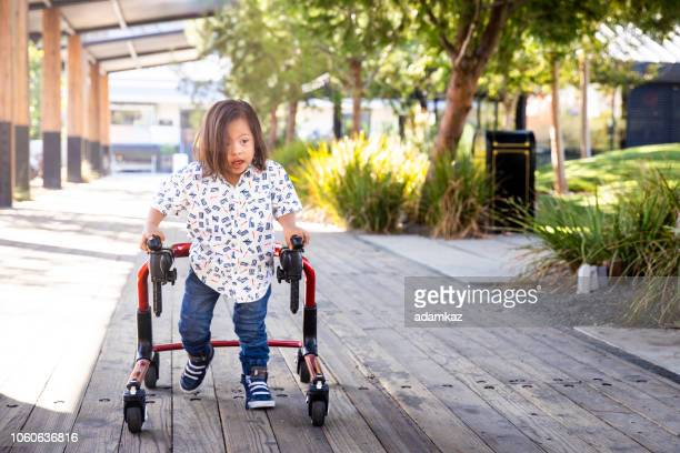 young boy with down's syndrome walking - disability stock pictures, royalty-free photos & images