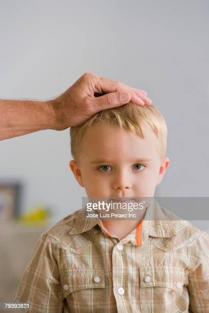 Young boy with father's hand on head