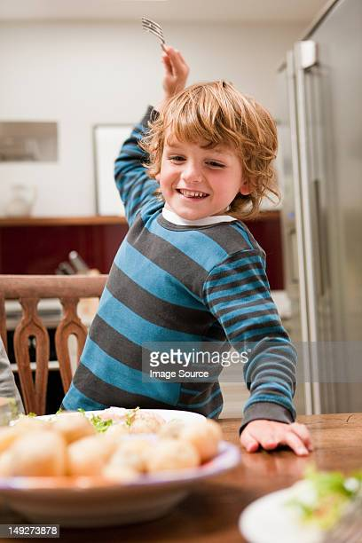 young boy with fork raised about to stab potato - children only stock pictures, royalty-free photos & images