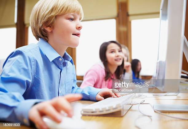 Young boy with friends using computer in classroom