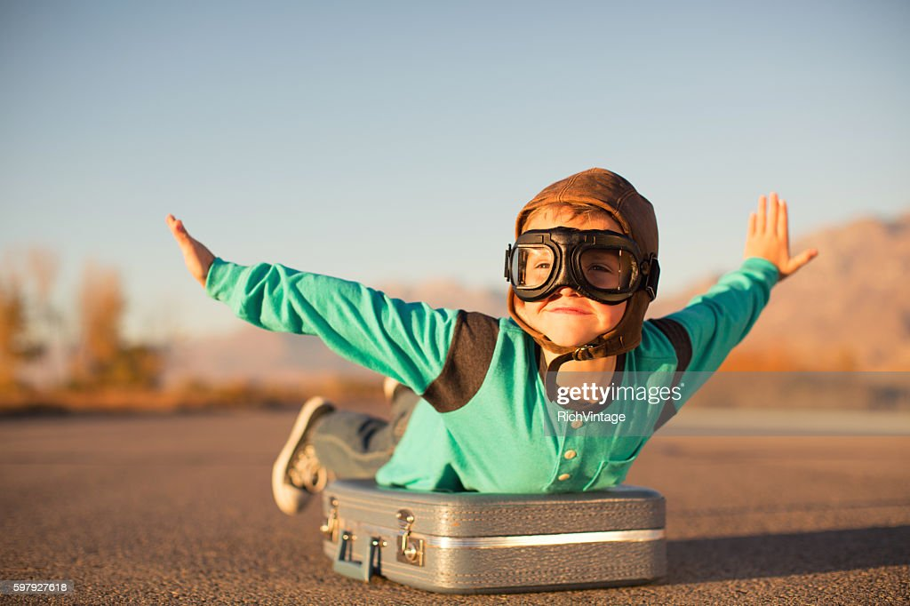 Young Boy with Goggles Imagines Flying on Suitcase : Stock Photo