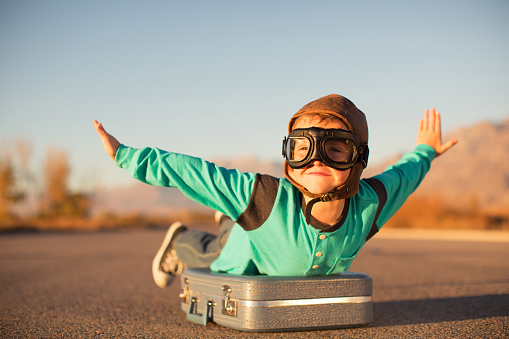 Young Boy with Goggles Imagines Flying on Suitcase - gettyimageskorea