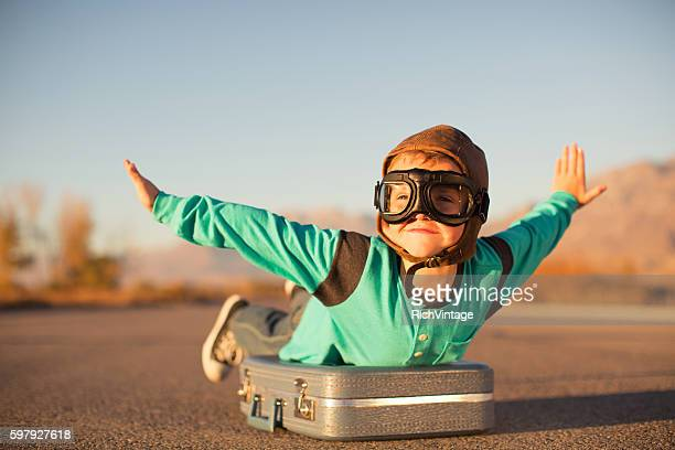 young boy with goggles imagines flying on suitcase - fliegen stock-fotos und bilder