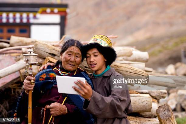 young boy with grandmother using digital tablet - pilgrims and indians stock photos and pictures