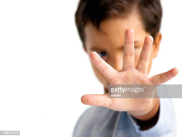 young boy with hand outstretched makes a stop gesture