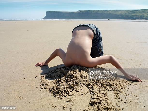 Young boy with head buried in sand on beach