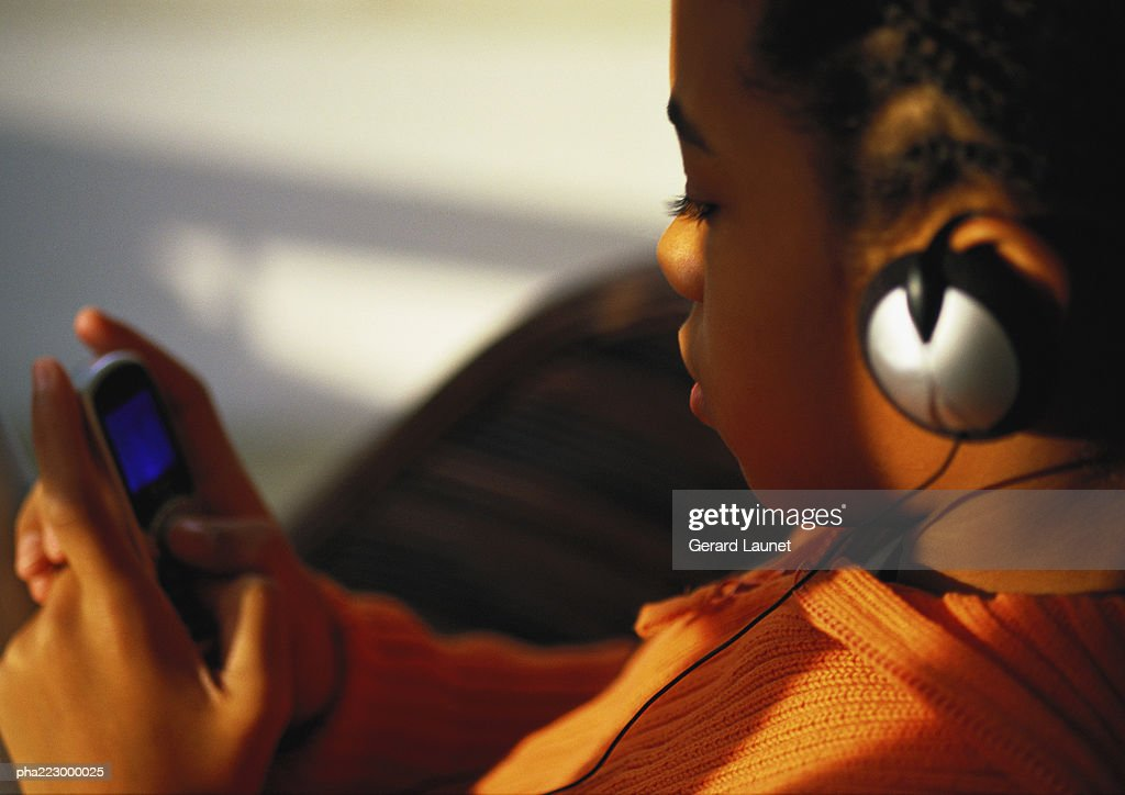 Young boy with headphones on looking at phone, close up. : Stockfoto