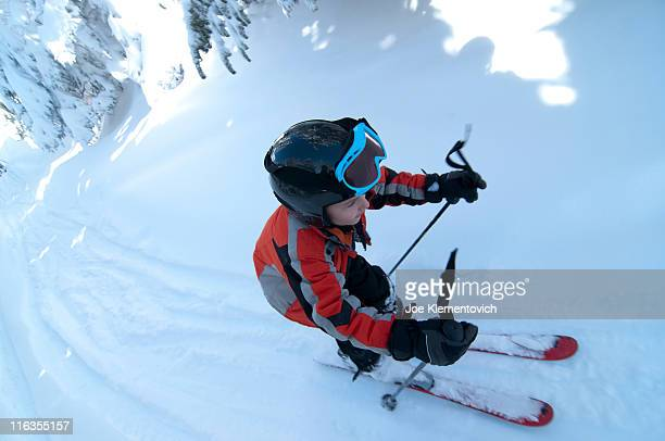 Young boy with helmet on alpine skiing on a bright sunny day.
