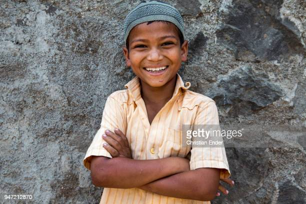 A young boy with his arms crossed in a yellow shirt is standing in front of a stone wall in a small village on March 28 2013 in Bijapur India He is...